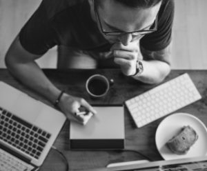 Black and white photo of man sitting in front of his computer with coffee