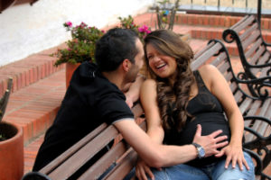 Pregnant woman on a bench with her husband putting his hand on her belly