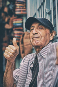 Elder man giving thumbs up to camera