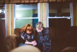 two women crying on a couch