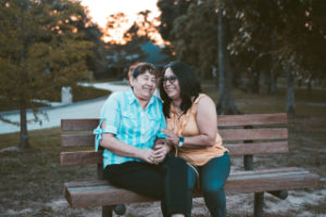 two women sitting on a park bench