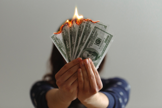 A person holding money that's burning