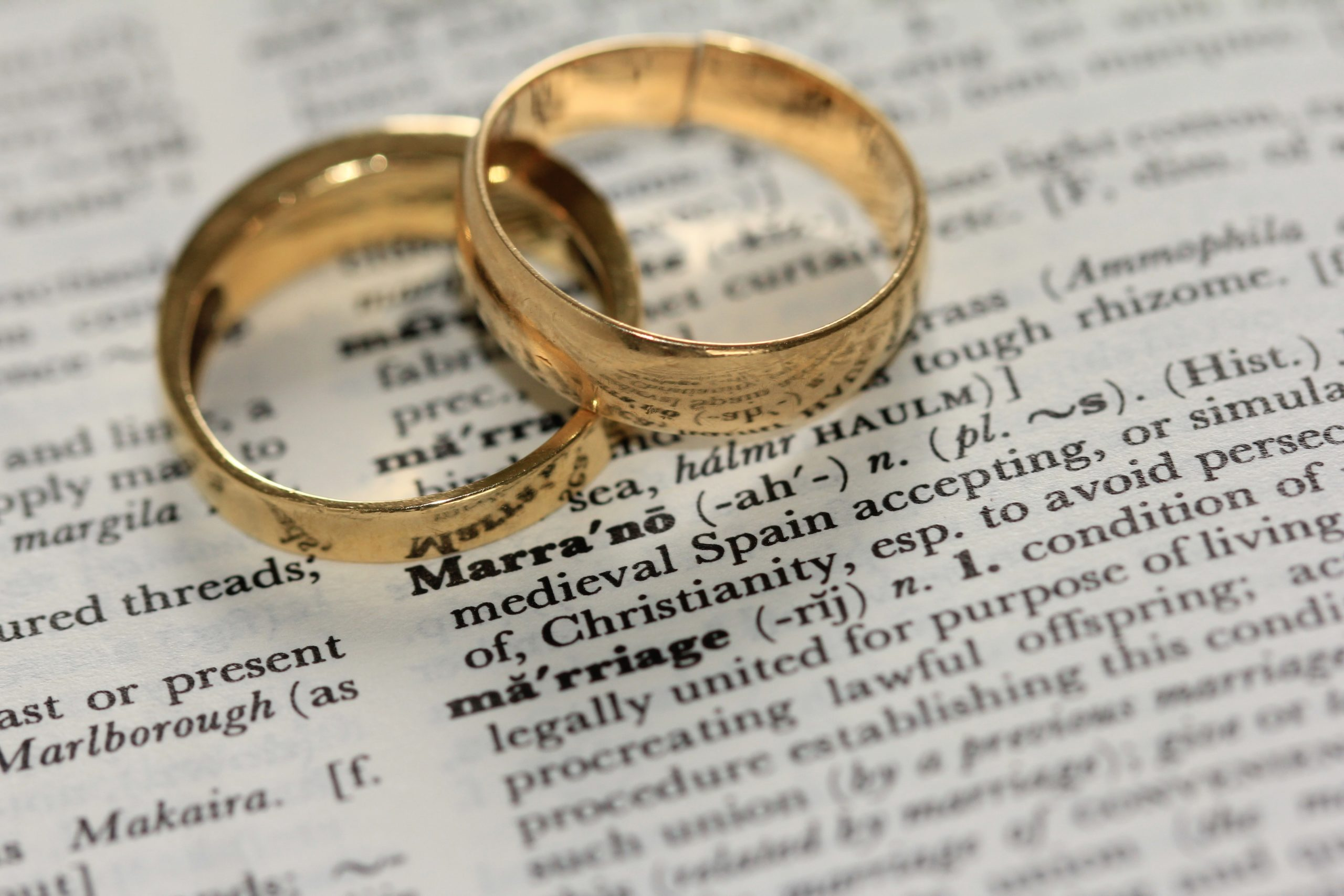 two rings sitting on a open dictionary over the word marriage